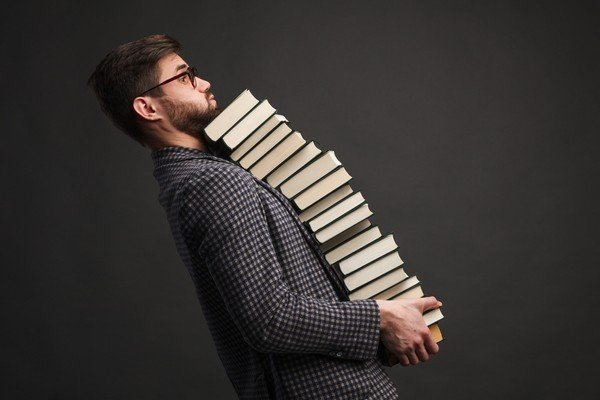 man carrying many books