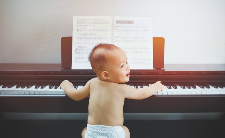 A baby boy playing the piano with the score